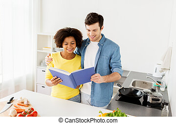 happy couple with cooking book at home kitchen - people,...