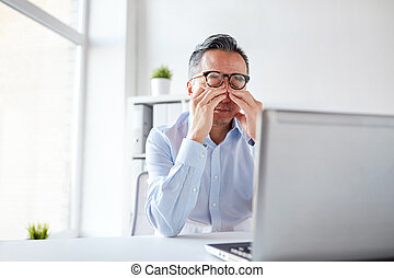 tired businessman in glasses with laptop at office -...