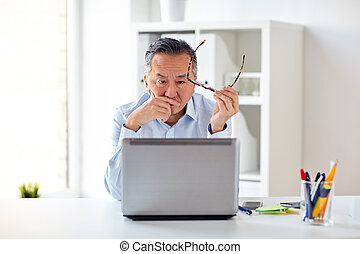 businessman with eyeglasses and laptop at office - business,...