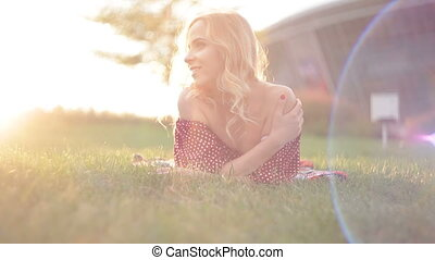 Young beautiful woman lies on the grass in the park.