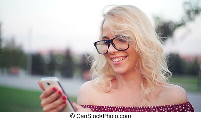 Beautiful young woman with glasses is talking on the phone.