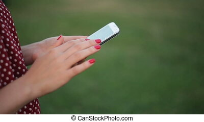Woman Using a Smart Phone in summer park