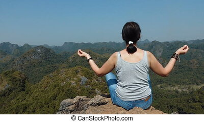 Attractive woman relaxing and meditating at the top of the mountain