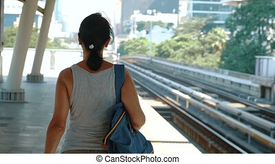 The woman walking on the platform and turns to the camera....