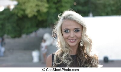 Elegant blonde with curly hair walking in the park and...