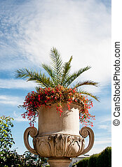 Large white vase with flowers on sky background with clouds on a Sunny day.