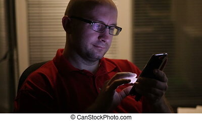 man in glasses works on a smartphone.