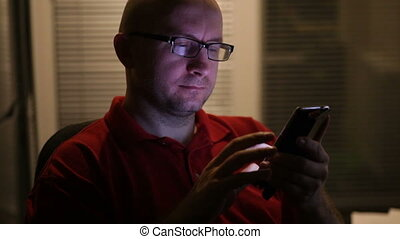 man in glasses works on a smartphone