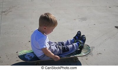 a small child riding on a skateboard. Active outdoor sports...