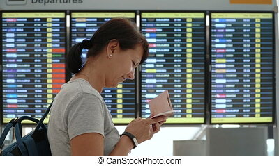 Tourist woman checking timetable at international airport....