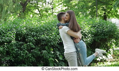 guy hugs and twirls in her arms pretty girl in the Park