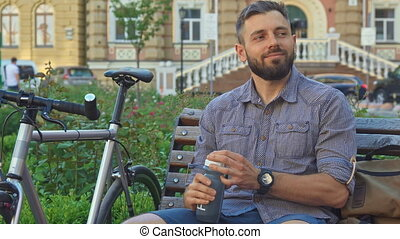 Cyclist drinks water on the bench