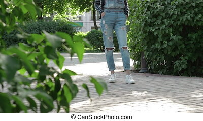 girl in denim overalls stands in the alley in the Park