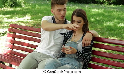 Guy watching pictures in mobile phone of his girlfriend on a...