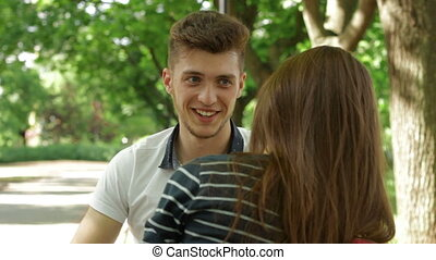 handsome man talking with brunette girl in the park on the bench