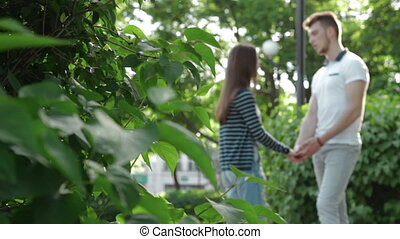 loving couple in the Park holding hands and talking at warm...