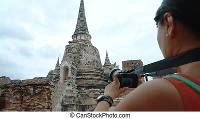 Woman is shooting a video of the temple - Woman is shooting...