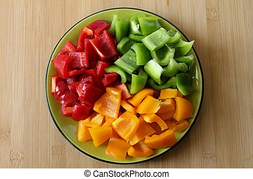 A plate filled with peppers fresh colors and cut into...