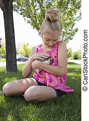 Young girl holding a pet hedgehog outside in the summer