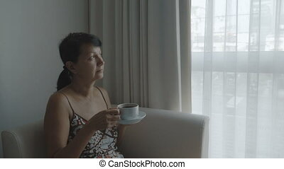 Woman drinking coffee near the window.