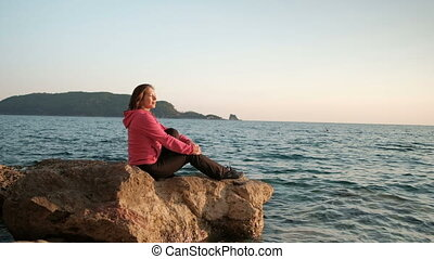 Young woman sits on rock by water outdoors. With smile she...