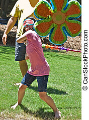 Girl Hitting Pinata - A young girl taking a swing at a...