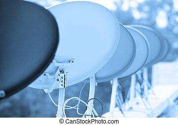 Many dish antennas arranged in a row.