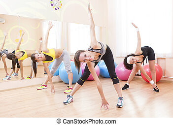 Fitnes and Stretching Conceots and Ideas. Three Happy Caucasian Female Athletes in Good Fit Having Stretching Exercises in Gym.