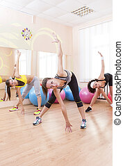 Fitnes and Stretching Conceots and Ideas. Three Happy Caucasian Female Athletes in Good Fit Having Stretching Exercises in Gym