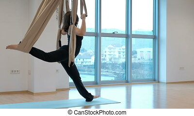 Young woman doing stretching with hammock for yoga indoors.