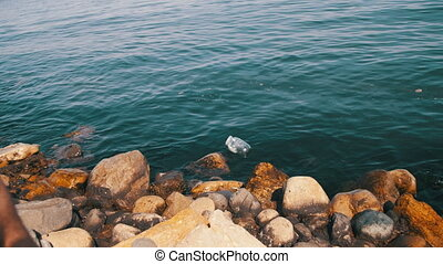 Garbage Floats in the Caspian Sea near the Stones on the...