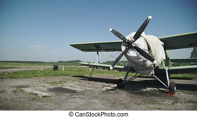 Old aircraft with a propeller for repair on the runway. The...