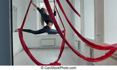 Slim female pole dancer doing twine with aerial silk. Slow...