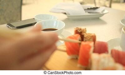 Someone eats sushi rolls. Close up. - Someone eats sushi...