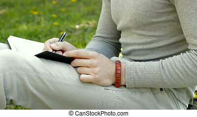 guy makes notes in a Notepad in the Park - close up of guy...
