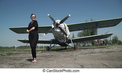 Woman pilot portrait in front of plane bomber. in a black...