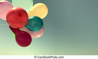 Multicolored balloons fly in the wind, vintage toning