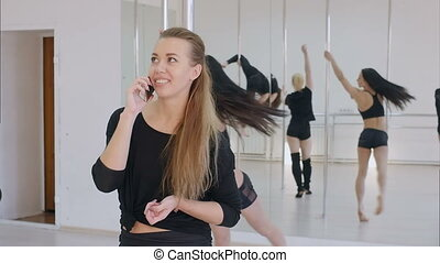 Young woman have a phone call during a pole dance class....