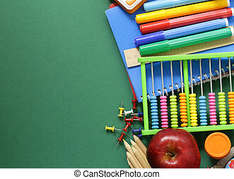 School supplies and apple on a green background