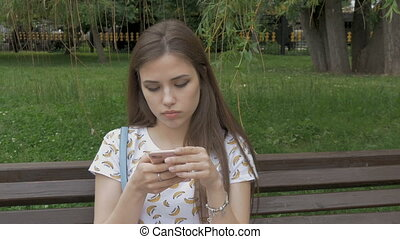 Young beautiful girl is sitting on a park bench, looking sms...