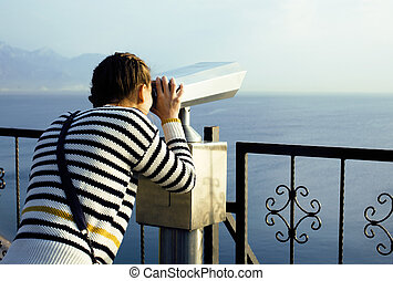 young woman looking through telescope at sea viewpoint in...