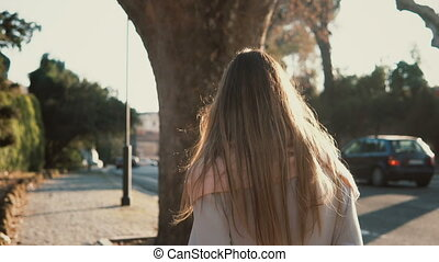 Back view of young woman walking alone at the city centre. Pensive female going near the road in bright sunny day.
