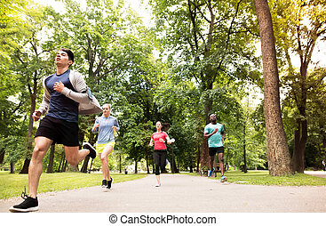 Group of young athletes running in green sunny park. - Group...