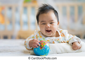 Newborn boy smile on the bed with world model