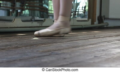 Ballet dancer in pointe on wooden floor - Close up feet of...