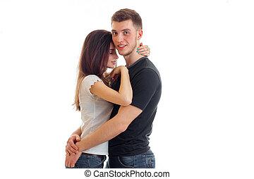 pretty young heterosexual couple hugging in studi