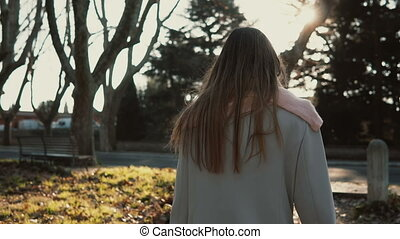 Beautiful young woman walking at park in bright autumn day....