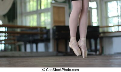 Ballet dancer stand on pointe in the ballet hall