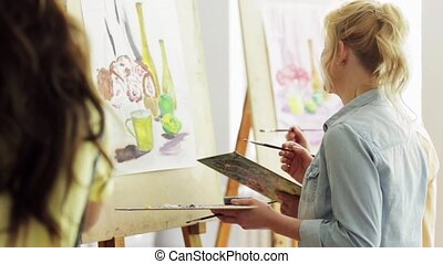 group of students painting at art school studio - art...
