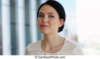 face of happy smiling young woman at office - business,...